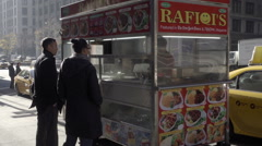 white man and black woman snacks from food truck in cold weather in fall NYC - stock footage