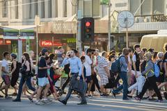 People walking across a busy crosswalk in Melbourne at sunset - stock photo