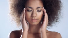 Portrait of a beautiful young African woman making face massage. Stock Footage