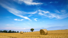 Stubble field with straw bales under blue sky with cirrus clouds - stock footage