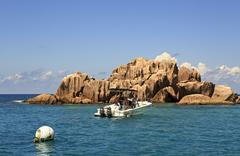 Boat with tourism near huge granite boulders of St. Pierre Island in the Indian Stock Photos