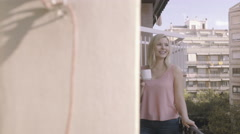 Young adult female enjoying view and drink on balcony in Barcelona, Spain Stock Footage