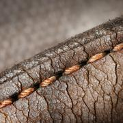 Close-up of old stiches in leather - stock photo