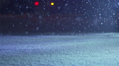 Snow falls on the ground in slow motion and covers road - stock footage