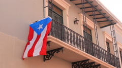 Colonial architecture hispanic balcony with flag in Old San Juan Stock Footage