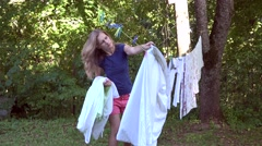 House keeper woman take off dried clothes from outdoor rope between trees. 4K Stock Footage