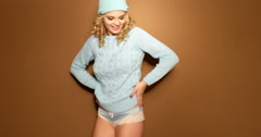 Smiling blonde woman in winter jumper and hat jumping on brown background Stock Footage