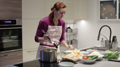 Young woman in kitchen preparing stuffed cabbage Stock Footage