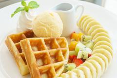 Belgian waffles with chocolate, bananas and strawberries. - stock photo