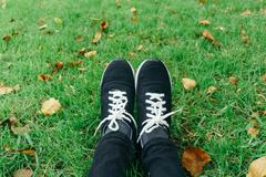 Youth sneakers on girl legs on grass during sunny serene summer. Stock Photos