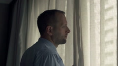 Young businessman unveil curtains and admire view from window Stock Footage
