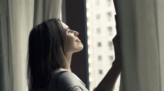 Young businesswoman unveil curtains and admire view from window Stock Footage