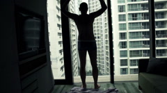 Young man stretching arms and admire view from window, super slow motion 240fps - stock footage
