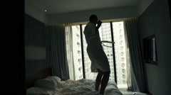Young man in bathrobe jumping on bed, super slow motion 240fps Stock Footage