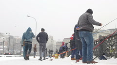 People on the Galata Bridge on a snowy winter day in Istanbul (Editorial) Stock Footage
