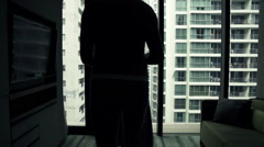 Man putting on shirt and admire vie from window, super slow motion 120fps Stock Footage