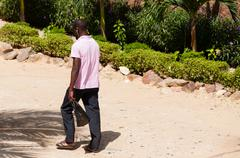 African man with pink polo shirt on dusty street in Dakar Stock Photos
