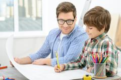 Cheerful father and son making  project - stock photo