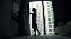 Young woman unveil curtains at home Stock Footage