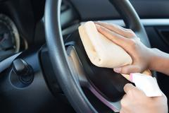 Close up hand cleansing car dashboard Stock Photos