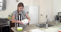 Young girl baking, sieving flour in kitchen, 4K Stock Footage