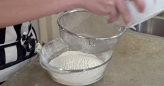 Baking girl sieving flour, close up Stock Footage
