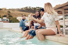 Friends partying by the pool toasting cocktails - stock photo