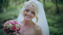 The bride with a bouquet in the wood - stock footage