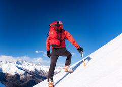 Stock Photo of Climber walks up a snowy slope. Winter season, clear sky.