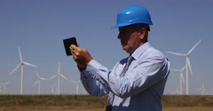 Energetic Industry Engineer Check Windmills Spin Speed Rotation Use Touch Pad Stock Footage