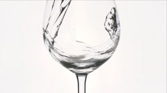 Water splash is falling into a wineglass - stock footage