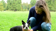 young attractive happy woman fondle french bulldog in the park - caress  - stock footage