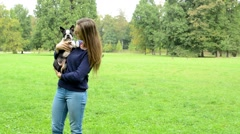 Young attractive woman carries french bulldog in the park - she kiss him  Stock Footage