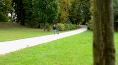 Young attractive woman walks french bulldog in the park without leash - dog walk Stock Footage