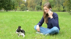Young attractive woman sits in the park and call with friend through smartphone Stock Footage