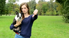 young attractive woman hug french bulldog and show thumb down - disagree - stock footage
