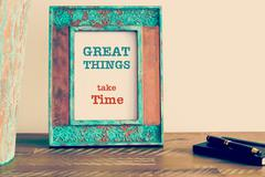 Motivational quote written on vintage photo frame GREAT THINGS TAKE TIME - stock photo