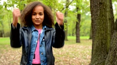 Young african happy girl with fluffy hair shows thumbs up as agree - eye contact Stock Footage