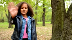 Young african beautiful happy girl waves for greeting in the park - eye contact  Stock Footage
