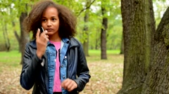 Young african chatty smile girl talks with friend through the smartphone Stock Footage