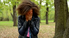 young sad african girl cry and cover her face with hands in the forest  - stock footage
