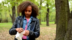 Young beautiful ill african girl blow her nose in tissue in the forest Stock Footage