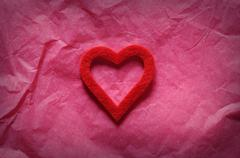 Red heart on pink paper.From above - stock photo