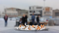 Ashtray with cigarette butts on city background Stock Footage