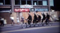 1964: Old timey police officer riding 5 person bike at parade. BUFFALO, NEW YORK Stock Footage