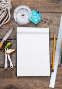 writing-book with fishing tackles and design tools on wooden board - stock photo