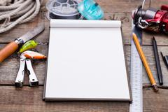 Writing-book with fishing tackles and design tools on wooden board Stock Photos