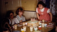 1962: Birthday girl blows out cake candles at home party. BUFFALO, NEW YORK - stock footage