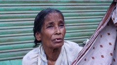 Poor, elderly Bengali lady laments and looks around Stock Footage
