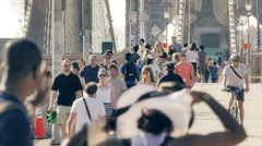 Pedestrians people walk crowd Brooklyn Bridge New York City NYC sunny day - stock footage